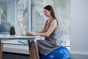 Female executive sitting on exercise ball while using laptop at desk