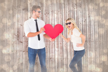 Cool young couple holding red heart against light glowing dots design pattern