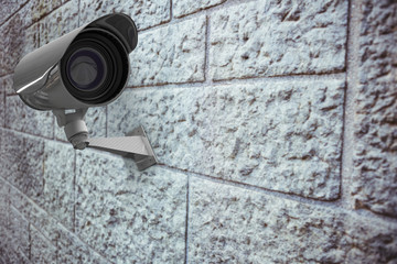 CCTV camera against grey brick wall