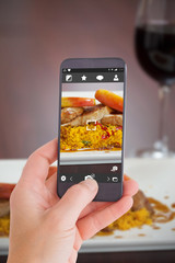 Female hand holding a smartphone against front view of couscous dish with meat and red wine