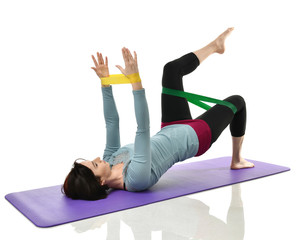 Mother woman exercising doing postnatal workout. Female fitness instructor holds legs in gym and workout exercises