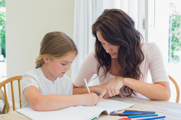 Woman assisting daughter in homework