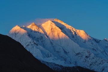 Mountain peak with first sunlight during sunrise on top in the morning. Rakaposhi mountain peaks in Pakistan