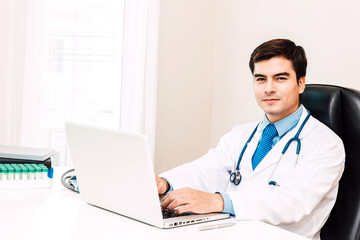 Doctor smiling and looking at camera with stethoscope working on laptop computer in hospital.healthcare and medicine