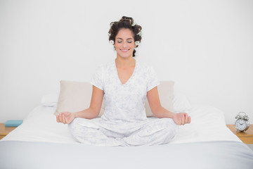 Smiling natural brunette sitting in lotus pose