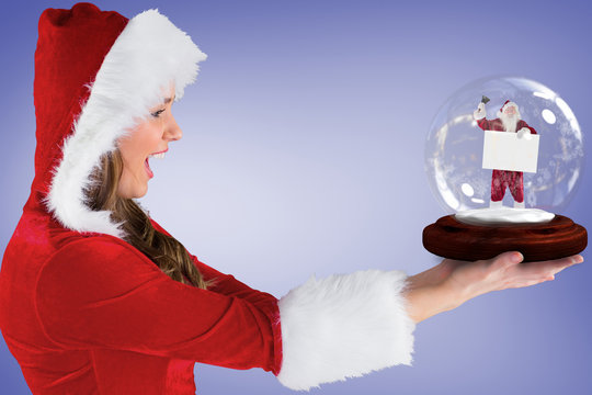 Composite image of sexy santa girl holding snow globe against purple vignette