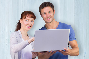 Couple using a laptop together against wooden planks