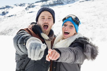 Couple in jackets pointing at the camera on snow covered landscape