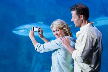 Happy couple taking a picture of fishes
