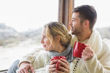 Couple in winter wear with cups looking out through window