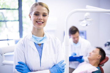 Portrait of smiling dentist standing  with arms crossed