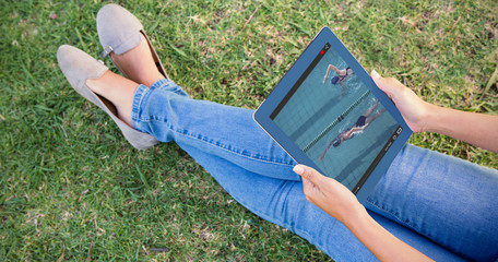 View of lecture app against woman using tablet in park