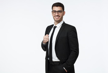 Half-length portrait of handsome Caucasian guy dressed in black suit, white shirt and tie isolated on gray background looking attentively through glasses and smiling positively and confidently