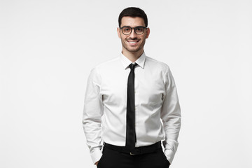 Half-length portrait of young European Caucasian man pictured isolated on grey background dressed in white T-shirt and tie and wearing glasses showing positive smile and readiness to develop