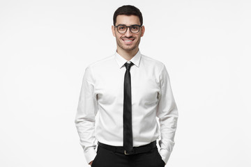 Indoor portrait of handsome European businessman pictured isolated on white background dressed in white formal shirt and black tie standing in front of camera, feeling positive, confident and calm
