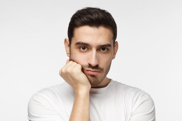 Closeup photo of young handsome Caucasian man isolated on grey background dressed casually, pressing hand to chin looking bored, exhausted and disappointed, feeling helpless and upset facing problems
