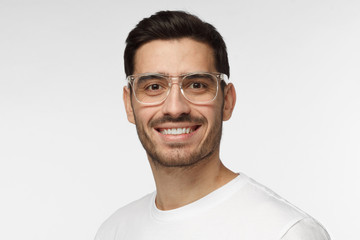 Studio portrait of confident European Caucasian man pictured isolated on gray background wearing casual clothes and plastic safety glasses showing happy friendly smile, willing to communicate