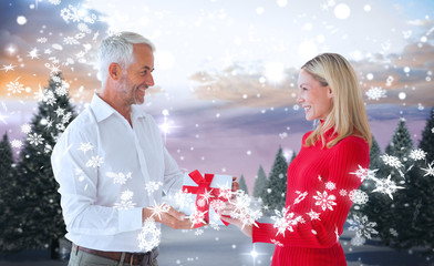 Loving couple with gift against snowy landscape with fir trees