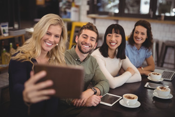 Young woman taking selfie with friends from tablet at cafe