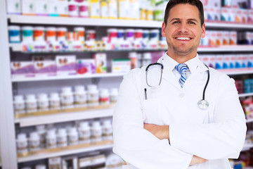 Handsome doctor with arms crossed against close up of shelves of drugs