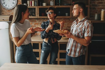 Young man treating his friends with homemade pizza. People enjoy
