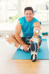 Sporty man stretching hand to leg in fitness studio against fitness interface