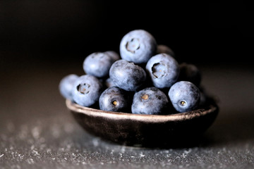 Blueberry .Moody Food Photography.  blueberries in a  black clay cup on a black background. Dark Key. The harvest of blueberries.