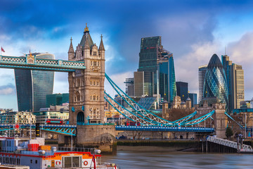 London, England - The famous Tower Bridge with iconic red double-decker buses on it and skyscrapers of Bank District at background