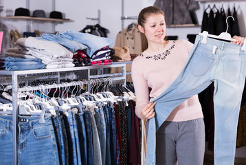 Positive young woman choosing stylish jeans