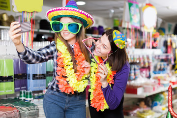 Happy women friends making funny photo in carnival outfits shop
