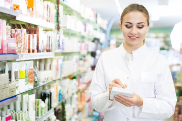 female pharmacist is inventorying medicines