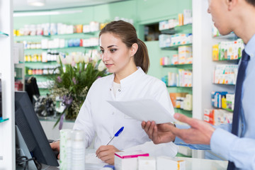 Woman pharmacist is recommending medicine for  male