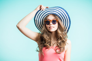 Beautiful girl in a summer hat and sunglasses smiling