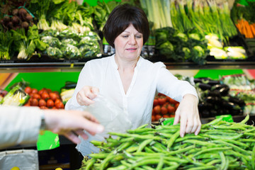 Middle aged woman choosing vegetables