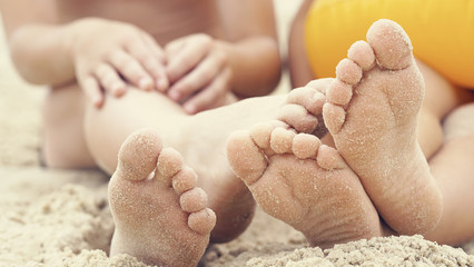 Children's feet are buried in sand. Happy holiday on th e sea coast.