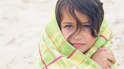 Cute little Latin girl at beach covered with green towel looking into the camera.