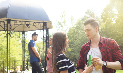 Smiling young couple with beer and looking at each other while two people barbecuing in the background.