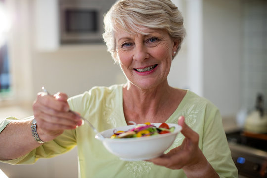 Senior woman holding vegetable salad in bowl