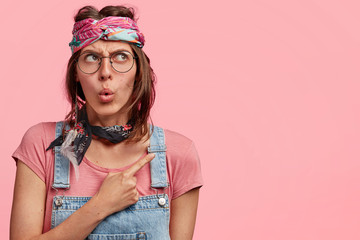 Indoor photo of amazed beautiful stylish hippie woman with headband and denim overalls, indicates at blank copy space for your advertising content, isolated over pink background. Wow, that`s amazing!