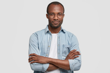 Image of confident attractive young African American male with pleased expression, keeps hands crossed, wears denim shirt and round spectacles, being content to recieve praisement from boss.