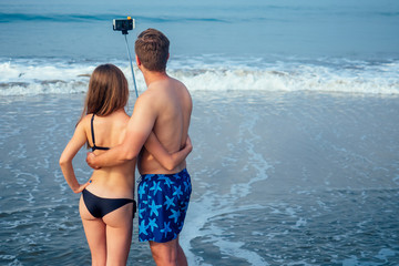 A loving couple on the beach is photographed with a self-stick