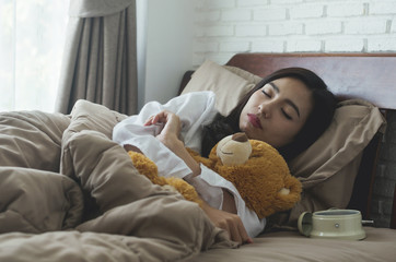 beautiful attractive woman sleeping comfortable on bed in the bedroom with teddy bear.