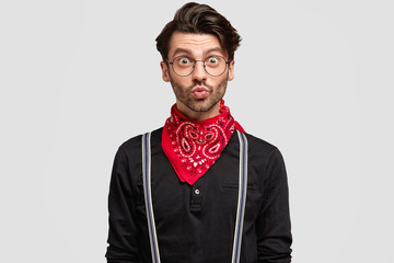 Attractive bearded male in stylish outfit, makes grimace and keeps mouth rounded, being pleasantly shocked as recieves compliment from girlfriend, isolated over white background. Style and people