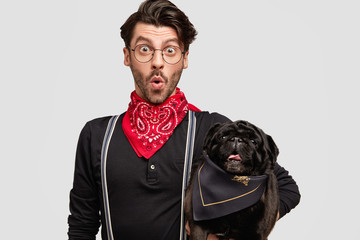 Photot of amazed young male dog trainer with his favourite pet, looks with surprisement at camera, pose together against white background. Unshaven hipster guy and black pug dog pose indoor.