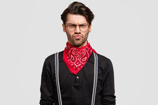 Portrait of grumpy handsome male frowns face in dissatisfaction, has discontent upset look, wears fashionable shirt, red bandana isolated over white background. Studio shot of man expresses negativity