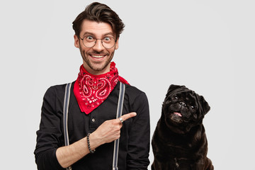 Leave in good hands. Glad male with attractive appearance indicates at black pug dog, advertises his pet, prepare together to dog show, isolated over white background. Look at my favourite animal