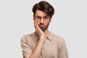 Studio shot of good looking fashionable guy wih upset expression, keeps hand on cheek, looks with gloomy expression directly into camera, isolated over white background. People, style concept
