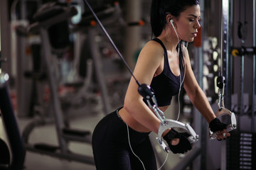 girl in sportswear working out and training shoulders with exercise machine crossover in gym