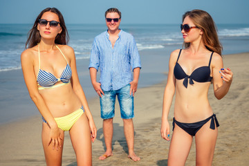 man looks at two young and beautiful women on the beach