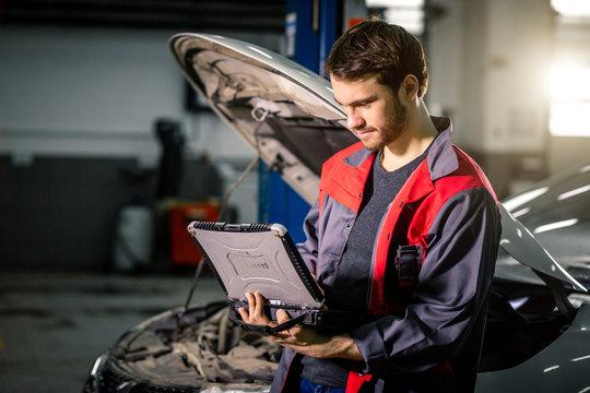 Mechanic using laptop on car at repair garage